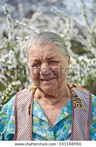 Smiling elderly woman in working clothes against a blossoming garden - stock photo