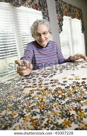 Smiling elderly woman putting together a jigsaw puzzle. Vertical shot. - stock photo