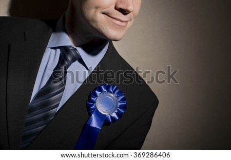 Smiling Election Candidate Wearing Blue Rosette - stock photo