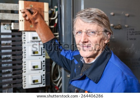 Smiling electrician repairman with pliers is on the work place - stock photo