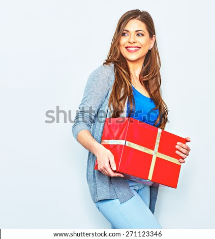 Smiling emotional Woman hold gift box. Big smile with teeth. Emotion of happy beautiful girl. White wall background. Red gift box.  - stock photo