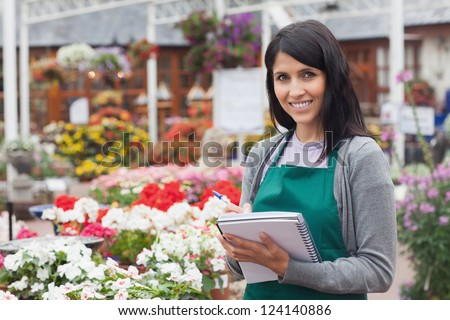Smiling employee making notes on the flowers in garden center - stock photo