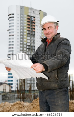Smiling engineer builder with blueprint at construction site - stock photo