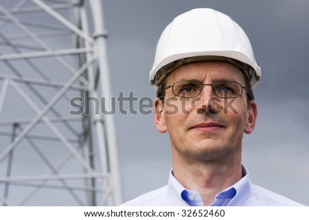 Smiling engineer in front of construction of steel - stock photo