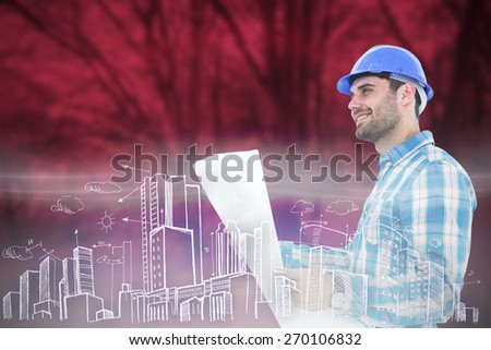Smiling engineer looking away while holding blueprint against purple forest - stock photo