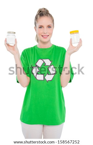 Smiling environmental activist wearing recycling tshirt holding jars on white background - stock photo