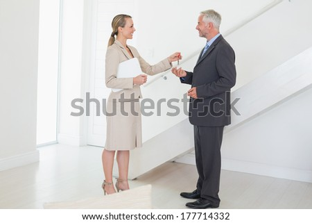 Smiling estate agent handing over keys to customer in empty house