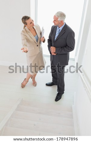 Smiling estate agent showing stairs to potential buyer in empty house
