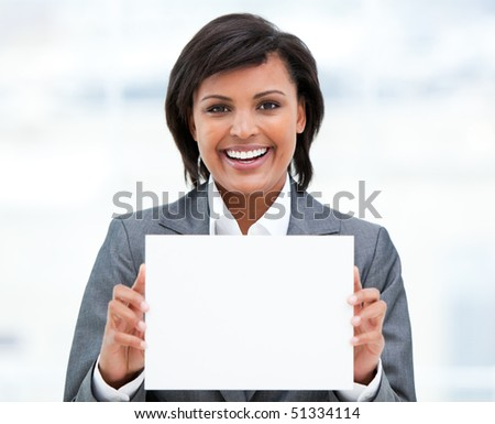 Smiling ethnic businesswoman holding a white card in the office - stock photo