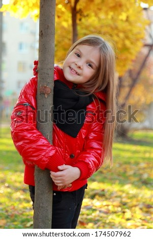Smiling european adorable young girl wearing red jacket at autumn park/Image of pretty kid outdoors