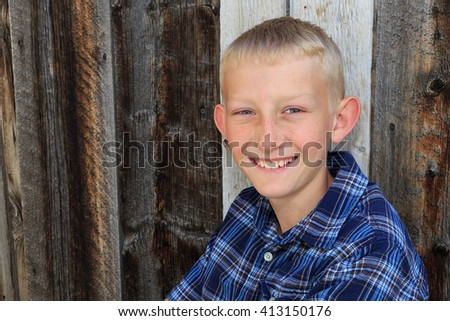 Smiling everyday boy with a barn wood background. - stock photo