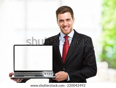 Smiling executive holding a laptop - stock photo