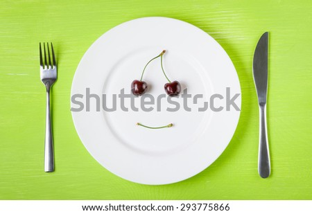 Smiling face of cherries on a white plate, knife and fork on a bright green table. The concept of a raw food diet, vegetarian, healthy eating, diet, weight loss, good mood