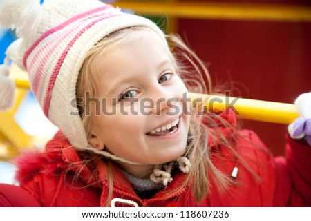 Smiling face of little girl on outdoor playground - stock photo