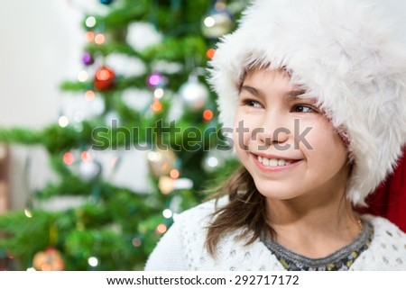 Smiling face on young pretty girl in white Santa hat, copyspace - stock photo
