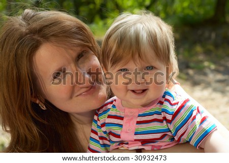 smiling faces of mother and her baby walking outdoor