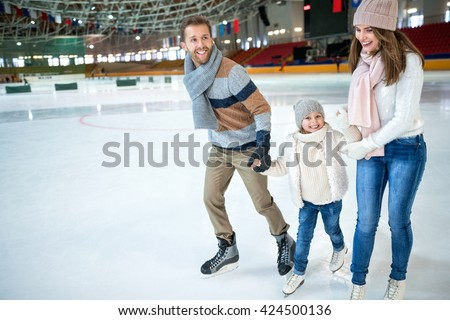 Smiling family at ice-skating rink - stock photo