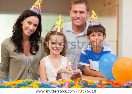 Smiling family celebrating daughters birthday together - stock photo