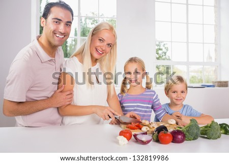 Smiling family cutting vegetables together in the kitchen