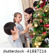Smiling family decorating a Christmas tree with boubles in the living-room - stock photo
