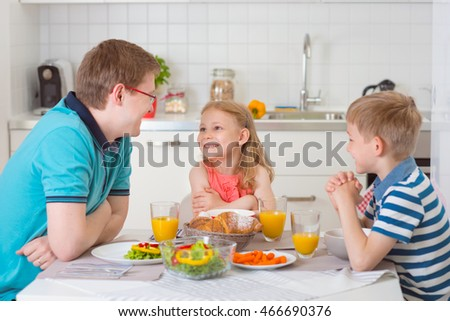 Smiling family eating breakfast together in kitchen