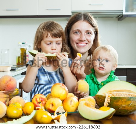 Smiling family eating melon and other fruits over  table at home interior - stock photo