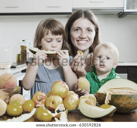 Smiling family eating melon and other fruits over  table at home interior