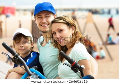 Smiling family having rest after cycling on the beach - stock photo