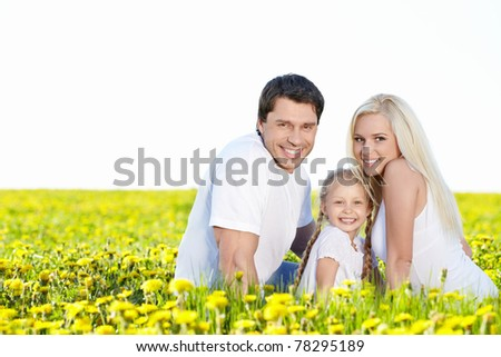 Smiling family in the lush field - stock photo