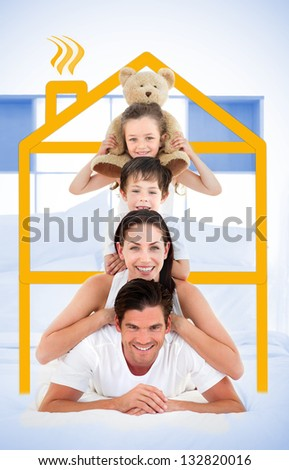 Smiling family leaning on each others shoulders in bed with yellow house graphic framing them - stock photo