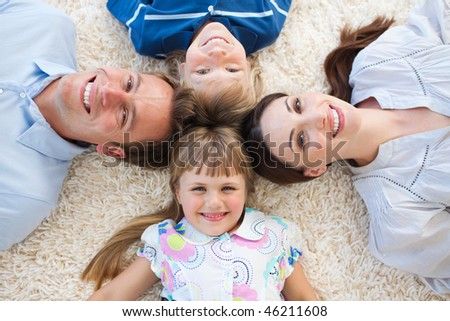 Smiling family lying in a circle on the floor
