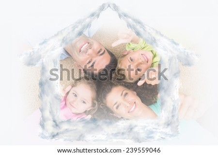 Smiling family lying on the rug in a circle showing thumbs up against house outline in clouds - stock photo