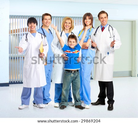 Smiling family medical doctors, nurses and young family. - stock photo