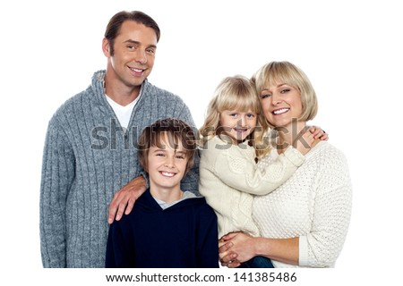 Smiling family of four posing in trendy winter wear