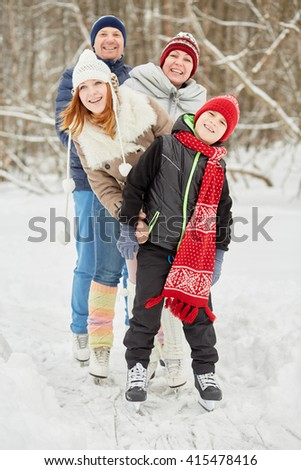 Smiling family of four stands on skates on ice pathway in winter park. - stock photo