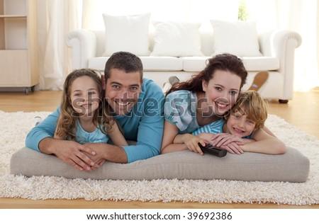 Smiling family on floor lying in living-room - stock photo