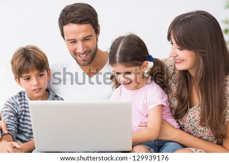 Smiling family on the couch using laptop