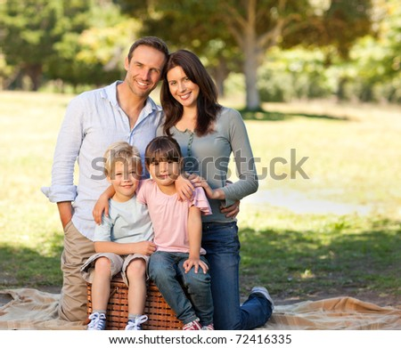 Smiling family picnicking in the park - stock photo