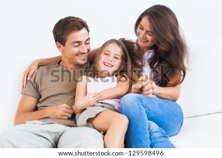 Smiling family playing together on a sofa in the living room - stock photo