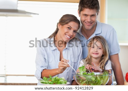 Smiling family preparing a salad in their kitchen - stock photo
