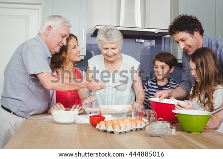 Smiling family preparing food in kitchen at home - stock photo