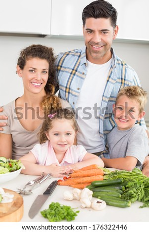 Smiling family preparing vegetables together at home in kitchen - stock photo