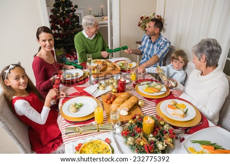 Smiling family pulling christmas crackers at the dinner table at home in the living room - stock photo