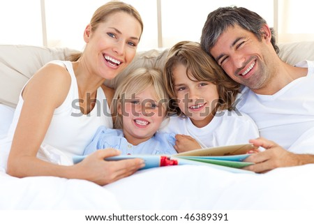 Smiling family reading a book  lying in bed