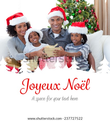 Smiling family sharing Christmas presents against joyeux noel - stock photo