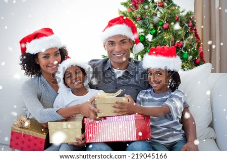 Smiling family sharing Christmas presents against snow falling