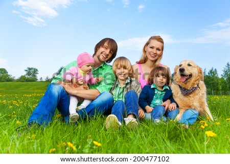 Smiling family sitting on green grass with dog - stock photo