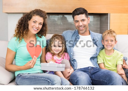 Smiling family sitting on sofa celebrating a birthday at home in living room - stock photo