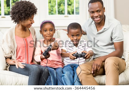 Smiling family sitting on the couch together playing video games - stock photo