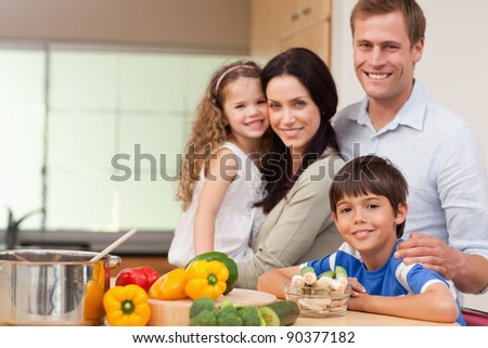 Smiling family standing in the kitchen together - stock photo